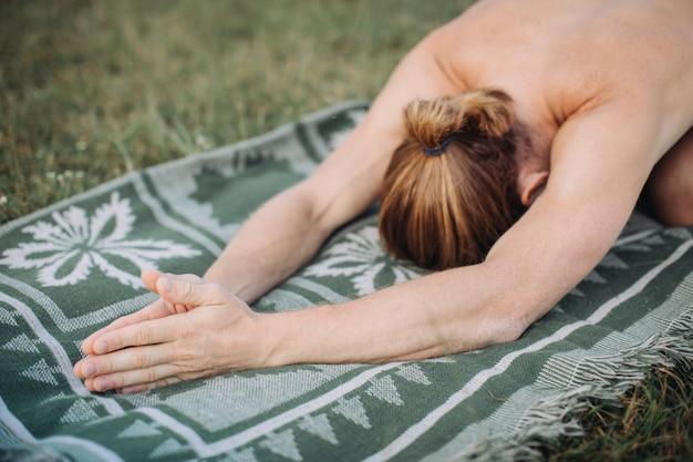 Desportivo homem praticando ioga ao ar livre Foto Premium