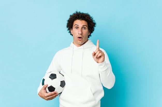 Desportivo homem segurando uma bola de futebol, tendo uma ótima idéia, conceito de criatividade. Foto Premium