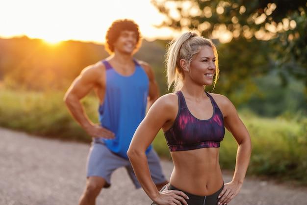 Desportivo par caucasiano fazendo exercícios de fitness na estrada rural no dia ensolarado de verão. foco seletivo na mulher. Foto Premium