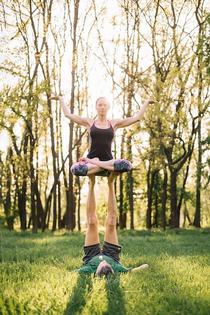 Desportivo, par, fazendo, acroyoga, exercícios, ligado, verde, glassy, terra Foto gratuita