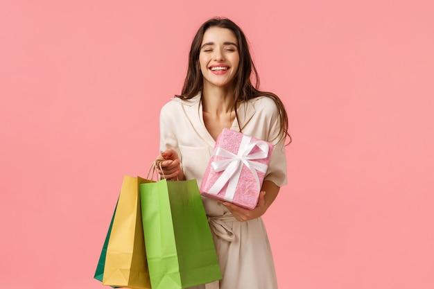 Despreocupado e encantado shoppaholic feminino, menina recebeu muitos presentes, segurando a sacola de compras e presente embrulhado bonito, fechar os olhos e sorrindo sonhadora desfrutando de festa de aniversário, parede rosa de pé Foto Premium
