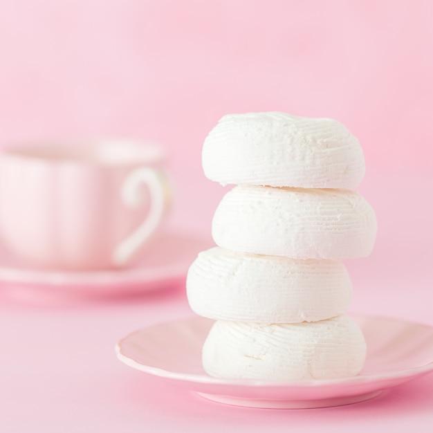 Dessrt branco do zéfiro na placa cor-de-rosa, xícara de café com leite no fundo do rosa pastel. Foto Premium