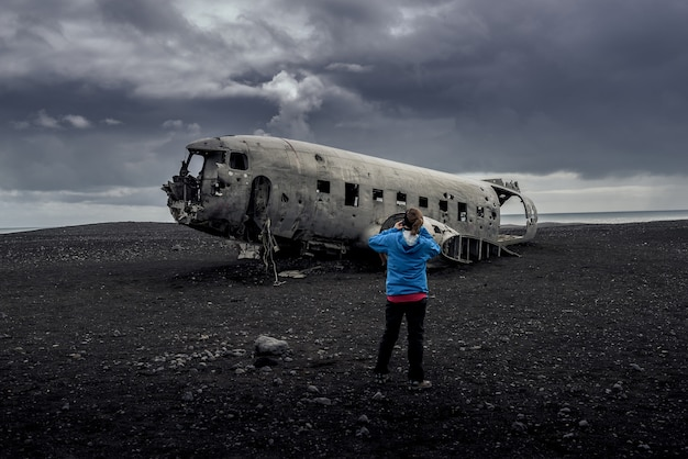 Destroços de avião na praia de areia preta na islândia Foto Premium