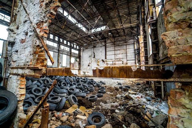 Destruiu a antiga fábrica com lixo e uma pilha de pneus de borracha usados dentro. Foto Premium