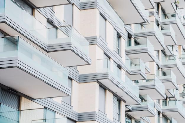 Detalhe da fachada de um edifício com varandas de vidro Foto Premium