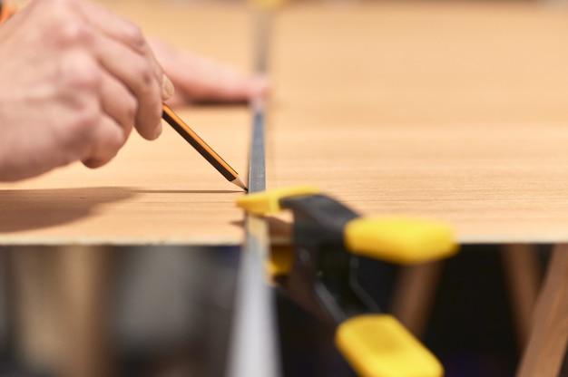 Detalhe da mão de um homem, fazendo uma marca com um lápis e um guia de metal em uma placa de madeira. o guia é mantido no lugar com um grampo. Foto Premium
