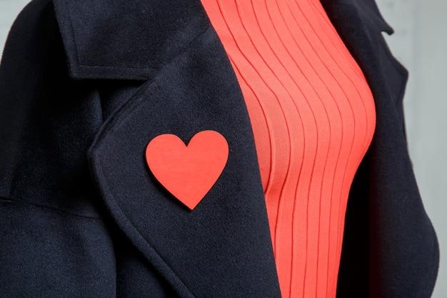 Detalhe da roupa feminina. broche em forma de coração em um casaco preto Foto Premium