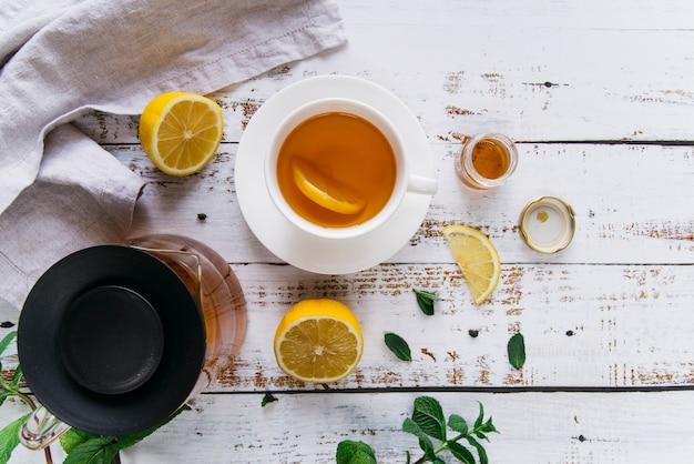 Detalhe da xícara de chá com limão e hortelã fresca na mesa de madeira branca Foto gratuita