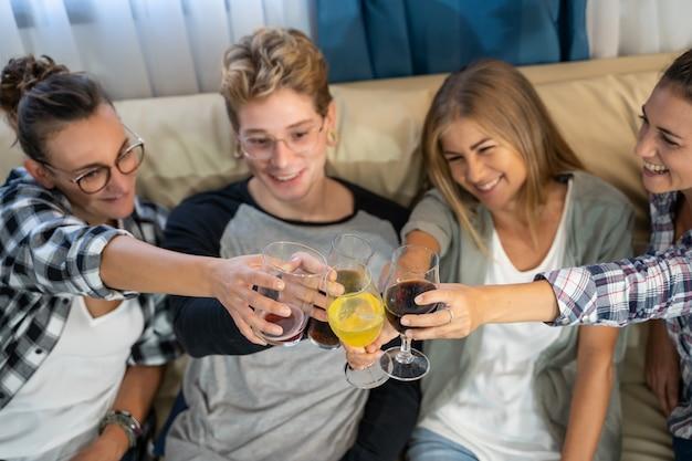 Detalhe das mãos de um grupo de jovens com óculos brindando Foto gratuita