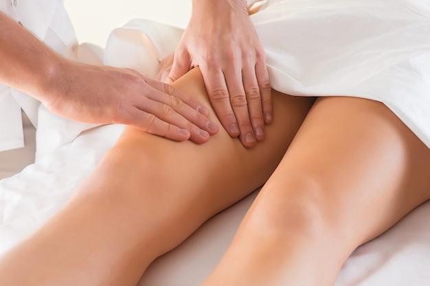 Detalhe das mãos massageando o músculo da panturrilha humana. Foto gratuita