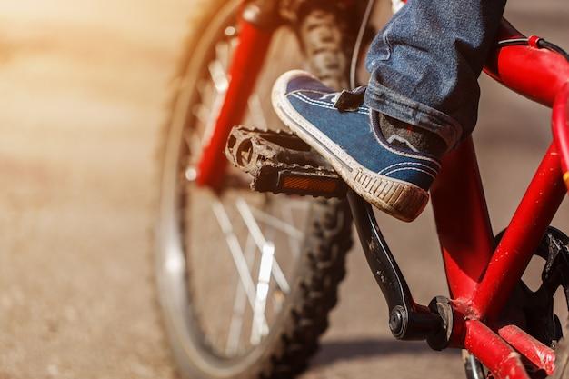 Detalhe de pés do ciclista da criança que montam a bicicleta em exterior na estrada ensolarada. closeup no pedal e pé Foto Premium