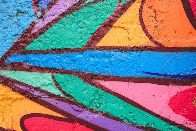 Detalhe de um grafitti anônimo da rua com muitas cores, fundo urbano alegre. Foto Premium