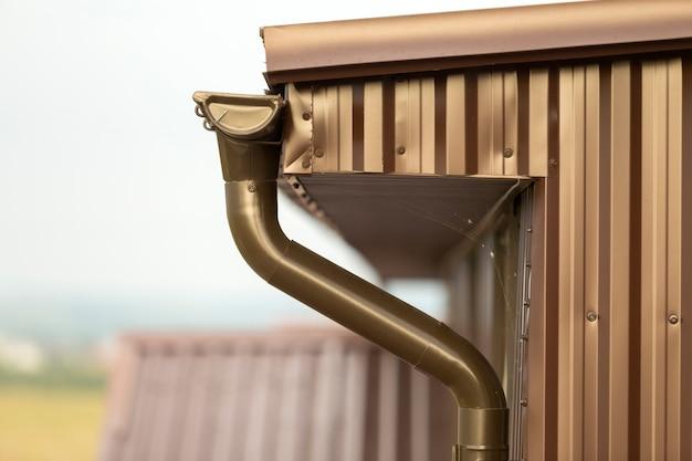 Detalhe do close-up de canto da casa da casa de campo com tapume das pranchas do metal e telhado com sistema da chuva da calha. Foto Premium