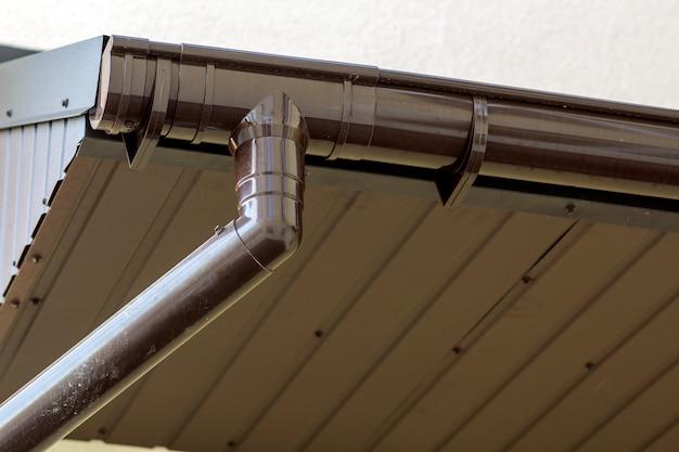 Detalhe do close-up de canto da casa da casa de campo com tapume marrom das pranchas do metal e telhado com sistema de aço da chuva da calha. cobertura, construção, instalação de tubos de drenagem e conceito de conexão. Foto Premium