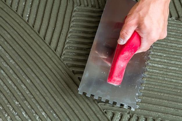 Detalhe do close-up de instalação de ladrilhos. melhoria home, renovação. mão de trabalhadores com flutuador entalhado para azulejo. adesivo para pavimentos em cerâmica, argamassa. Foto Premium