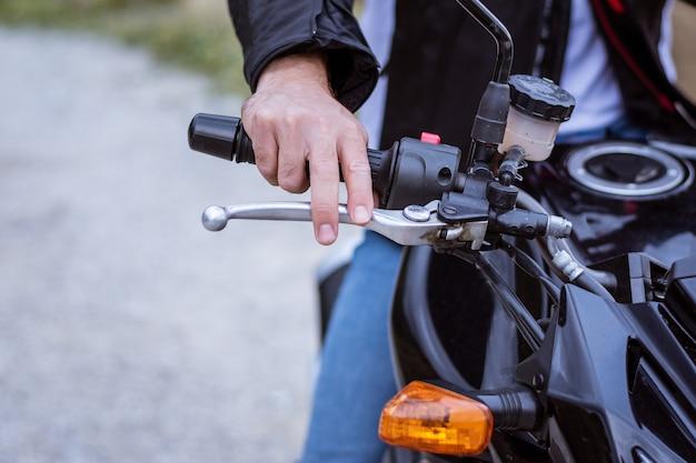 Detalhe do guidão de uma moto com o freio e a mão do piloto Foto Premium