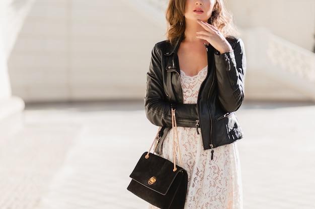 Detalhes da moda perto de uma mulher atraente andando na rua com roupa da moda, segurando bolsa suude, vestindo jaqueta de couro preta e vestido de renda branca, estilo primavera outono Foto gratuita