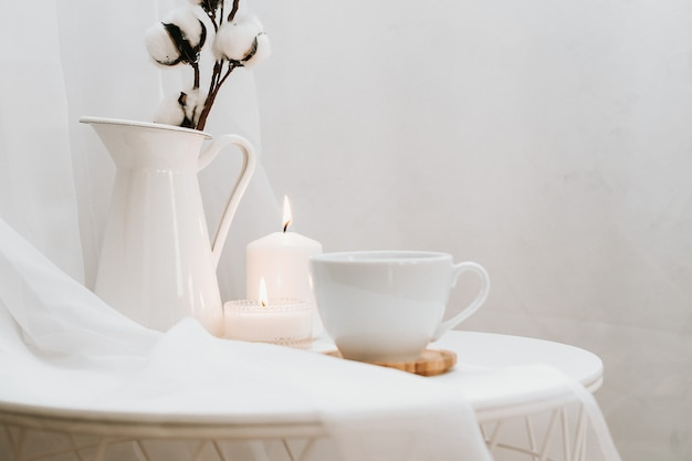 Detalhes da natureza morta no interior da casa da sala de estar em branco. xícara de café, algodão, vela, vaso. temperamental. copie o espaço para o texto Foto Premium