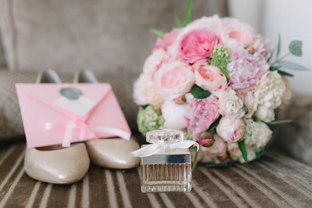 Detalhes da noiva: sapatos, bouquet rosa, perfumes e convites. Foto Premium