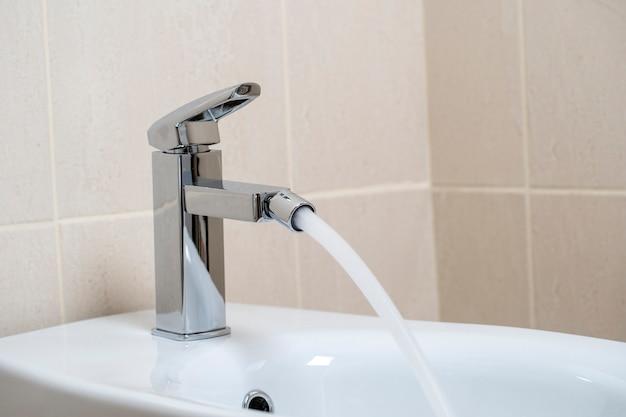 Detalhes de bidê de cerâmica branca com água da torneira em banheiro moderno com azulejos bege Foto Premium
