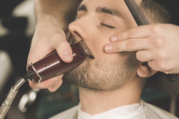 Detalhes de corte. closeup recortada de uma barba de aparar de barbeiro para seu cliente Foto Premium