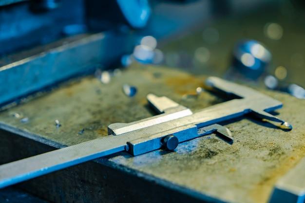Detalhes de metal estão sobre a mesa perto do torno na fábrica. Foto Premium
