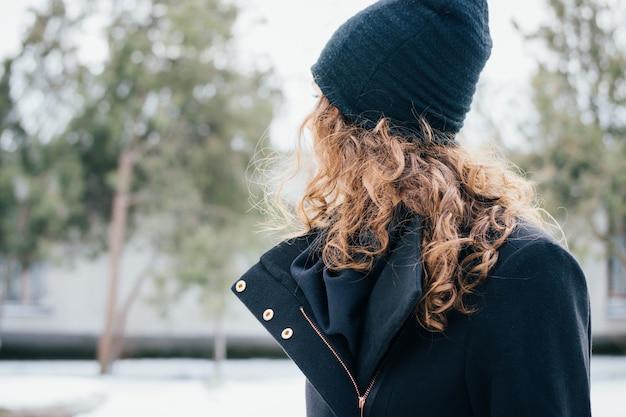 Detalhes de roupas femininas: menina com cabelo encaracolado em um casaco preto e boné closeup ao ar livre no parque Foto Premium