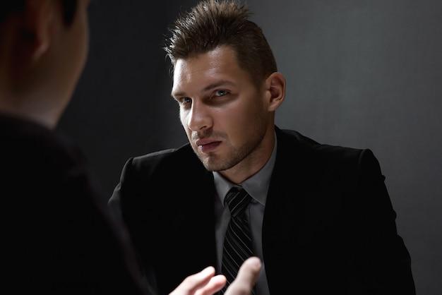 Detective entrevistando suspeito na sala de interrogatório escura Foto Premium