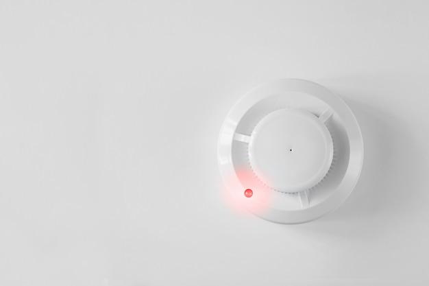 Detector de fumaça e detector de incêndio em um fundo branco Foto Premium