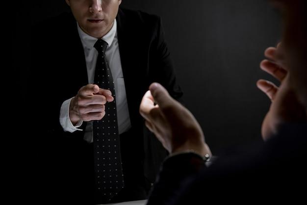 Detetive, apontar mão, para, criminal, homem, em, escuro, interrogatório, sala Foto Premium