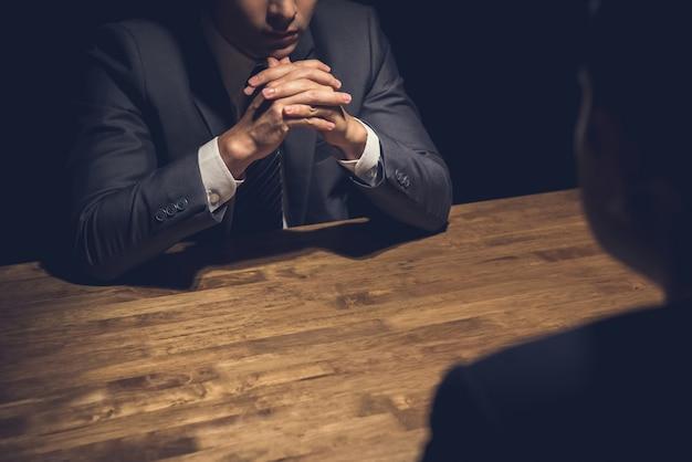 Detetive entrevistando suspeito no quarto escuro Foto Premium