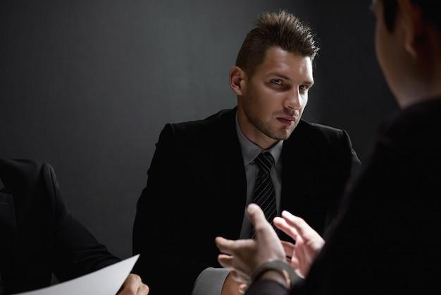 Detetives em sala de interrogatório com suspeito ou criminoso Foto Premium