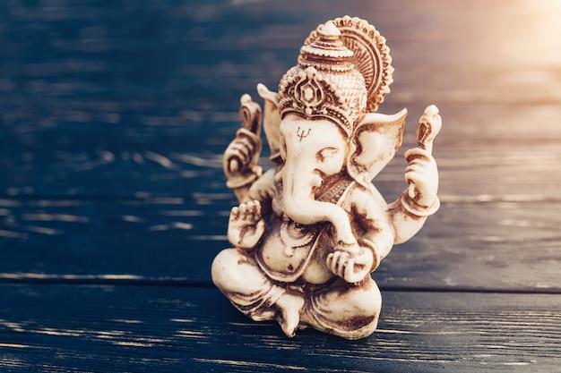 Deus hindu ganesh no fundo preto. estátua na mesa de madeira Foto Premium
