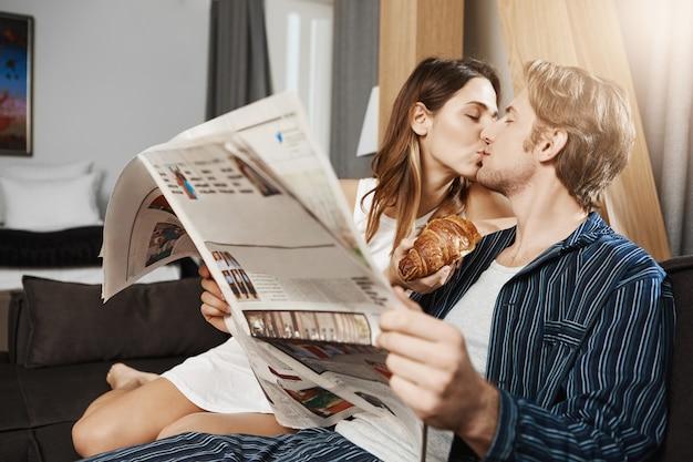 Dia comum de duas pessoas adultas apaixonadas, saindo juntas e passando o lazer em casa. homem quer ler jornal, mas a namorada o distrai com um beijo, oferecendo um croissant que ela segura na mão Foto gratuita