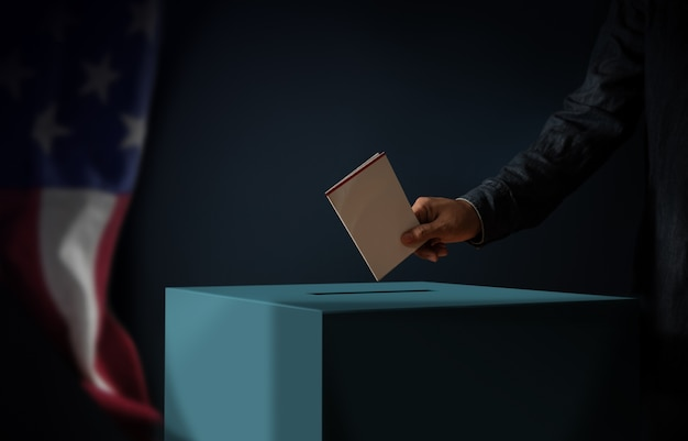 Dia da eleição no conceito de estados unidos da américa. pessoa colocando um cartão de voto na urna de votação. bandeira dos eua pendurada na parede. tom cinematográfico escuro Foto Premium