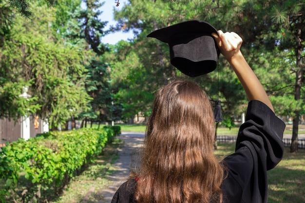 Dia da formatura, imagens de graduados estão comemorando a formatura colocar mão, um certificado e um chapéu na mão. Foto Premium