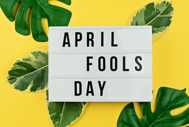Dia da mentira e folhas tropicais em amarelo Foto Premium