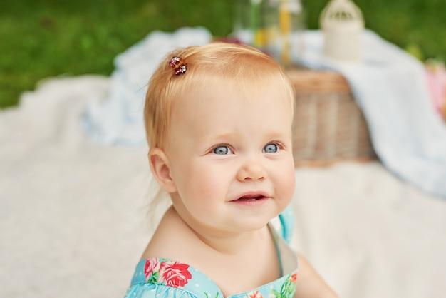 Dia da proteção das crianças, menina no parque senta-se em uma cesta em um piquenique de verão Foto Premium