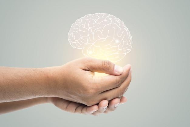 Dia da saúde mental. homem segurando ilustração do cérebro na parede cinza Foto Premium