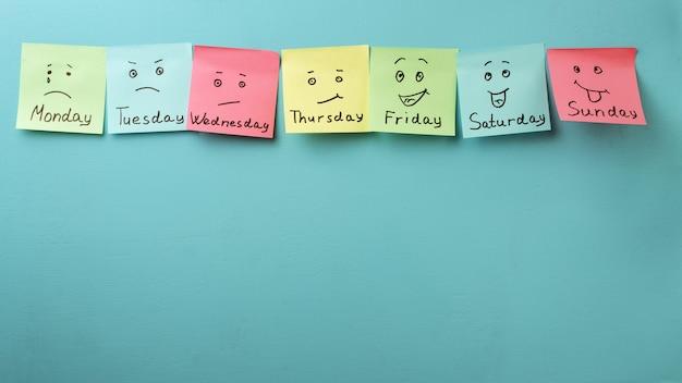Dia da semana e expressão facial. adesivos coloridos em um azul Foto Premium