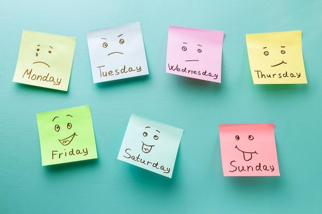 Dia da semana e expressão facial. adesivos coloridos em um quadro de avisos azul Foto Premium