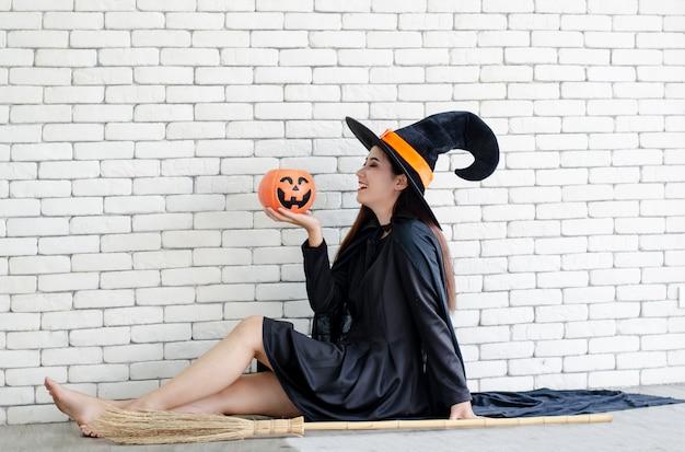 Dia das bruxas, bruxa, com, um, magia, abóbora, bonito, mulher jovem, em, bruxas, chapéu, e, traje Foto Premium