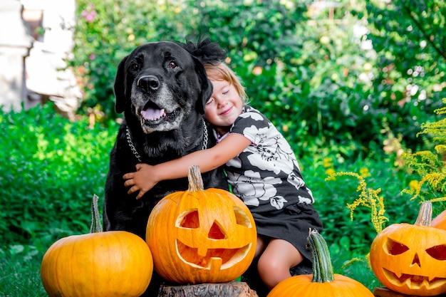 Dia das bruxas. criança vestida de preto perto de labrador entre decoração jack-o-lanterna, gostosuras ou travessuras. Foto Premium