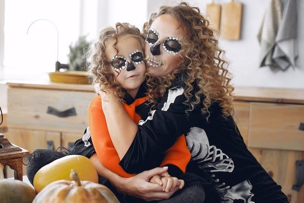 Dia das bruxas. mãe e filha em traje de halloween de estilo mexicano. família em casa com abóboras. Foto gratuita