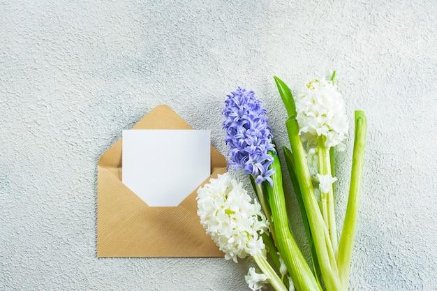 Dia das mães conceito de férias. jacintos flores e cartão vazio sobre fundo claro de concreto. cartão de primavera. configuração plana, vista superior, copie o espaço .. Foto Premium