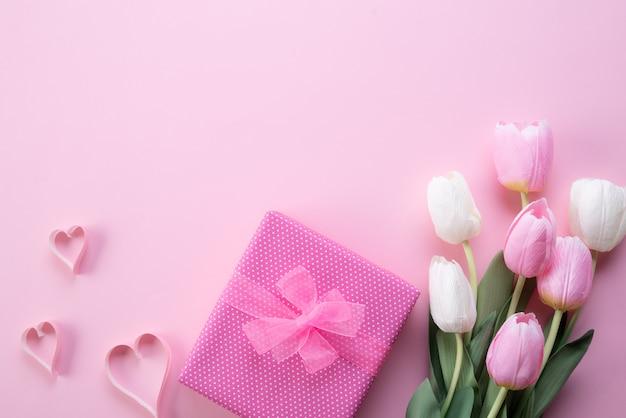 Dia das mães feliz com vista superior de flores tulipa rosa, caixa de presente e coração de papel Foto Premium
