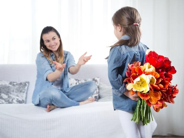 Dia das mães. filha com flores parabeniza a mãe Foto gratuita