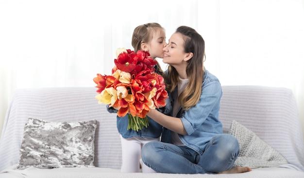 Dia das mães. filhinha com flores felicita a mãe dela Foto gratuita