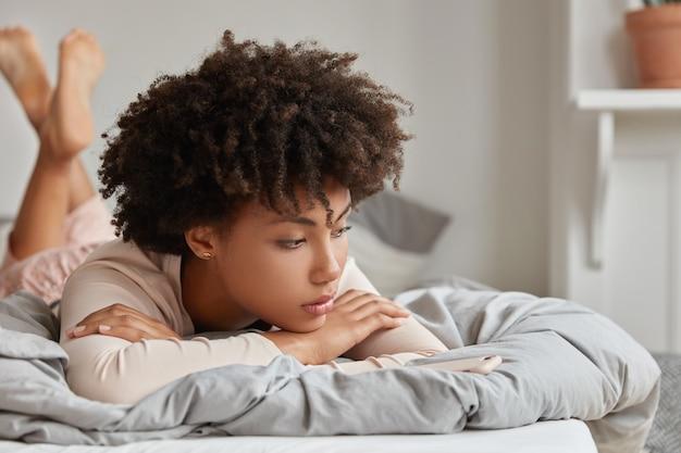 Dia de descanso e conceito de relaxamento. mulher pensativa, sonhadora, de pele escura, em pijamas, deitada na cama, gosta de conforto, sonha com algo depois de acordar, gosta do ambiente doméstico, sente-se solitária. Foto gratuita