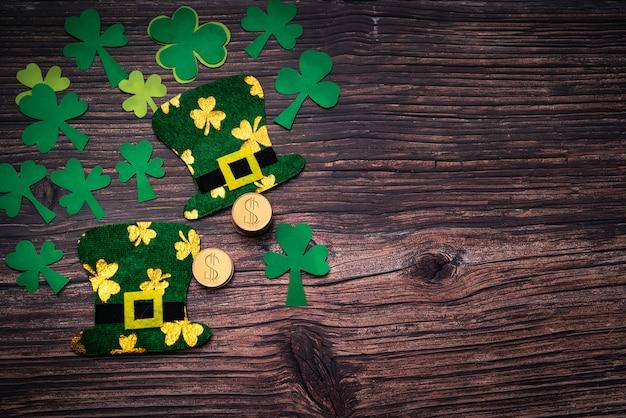 Dia de são patrício, moedas de ouro, chapéu festivo e verde trevos em madeira Foto Premium